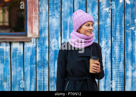 A young woman in a pink knitted hat, black coat and backpack  enjoys city, poses and drink coffee to go around blue wall. The concept of livestyle and - Stock Photo