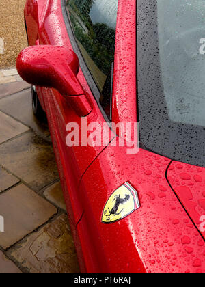 Ferrari wing mirror and logo in the rain showing bodywork from above - Stock Photo