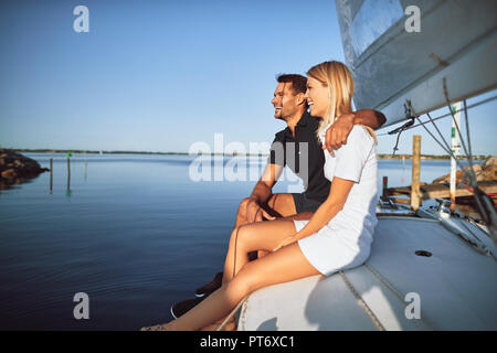 Laughing young couple having fun and enjoying the ocean view while sitting together on the deck of their boat - Stock Photo
