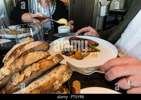 Lunch dishes at the Roux at the landau inThe Langham Hotel, UK. Fresh bread and steak - Stock Photo