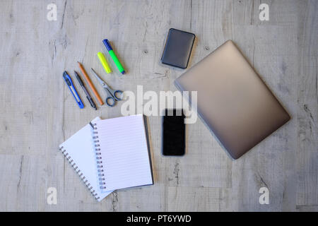 Top view of a project using laptop, hard drive, smartphone, notebooks and writing implements.  Flat lay of   educational and work equipment set on a l - Stock Photo