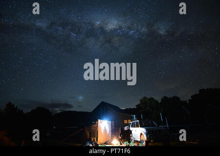 Camping Under the Milky Way stars Eaglehawk Neck tasmania with tent and four wheel drive (fwd) and communal camp building in background - Stock Photo