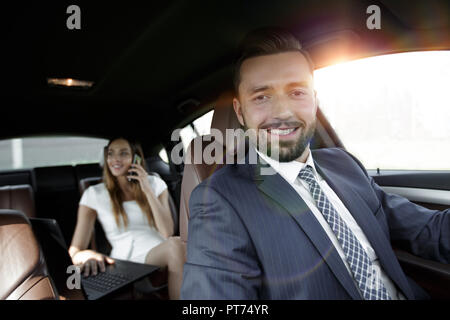 Young smiling handsome businessman in suit sitting in his luxurious car. - Stock Photo