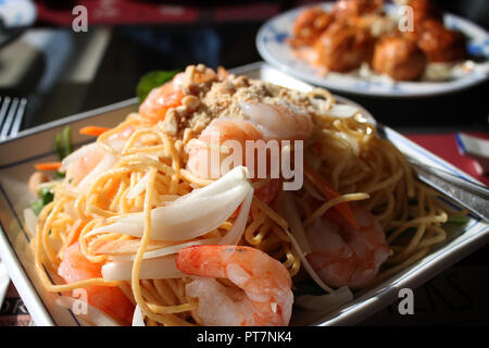 A platter of noodles with shrimps in a Chinese restaurant. - Stock Photo