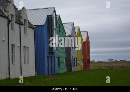 Multi coloured timber wood buildings in a row next to a traditional rendered brick stone building close to the sea at John O'Groats Caithness Scotland - Stock Photo