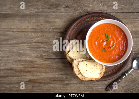 Tomato soup with bread and cheese on wooden table, top view, copy space. Homemade tomato soup in bowl. - Stock Photo