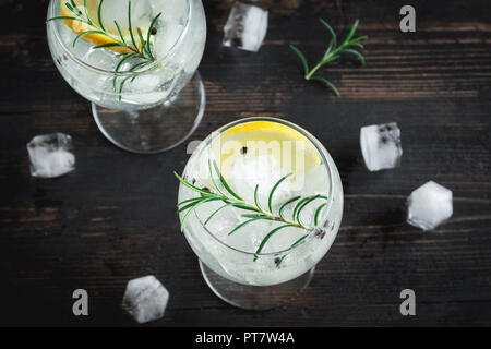 Alcohol drink (gin tonic cocktail) with lemon, rosemary and ice on rustic black wooden table, copy space, top view. Iced cocktail drink with lemon and - Stock Photo