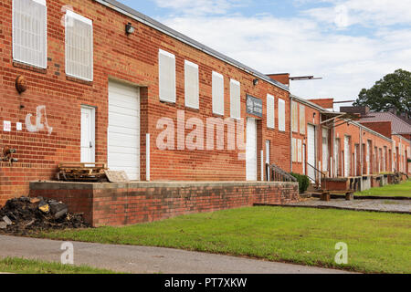 HICKORY, NC, USA-9/18/18:  A line of low loading docks and bay doors of an old industrial building. - Stock Photo