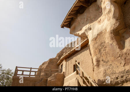 Painted frescos on walls outside caves cut into face of cliff at the Mogao Grottoes, or Caves of a Thousand Buddhas, Dunhuang, Gansu, China. - Stock Photo