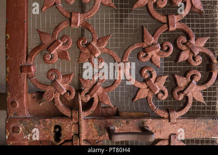 Decorative red oxide / brown painted old metal security gate with Fleur de lys detail at entrance to Chapel of Our Lady of Health at Kotor, Montenegro - Stock Photo