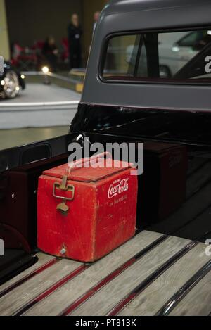 Antique rusted, red, Coca Cola (R) cooler in the bed of a black pickup truck. - Stock Photo
