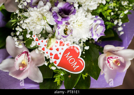 Text Love you Mom and heart shape, flowers background. Happy Mother's Day greeting card. Flat lay.bouquet with orchids flowers and lisianthus. mothers day. Natural flowers. Floral gift. Romantic love design - Stock Photo