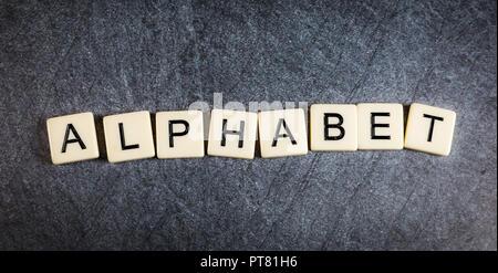 Letter tiles on black slate background spelling Alphabet - Stock Photo
