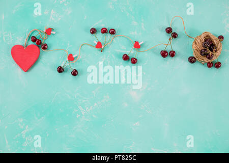 Love composition, flat lay for Valentines day. Red heart and sweet fresh cherries isolated on green backgrouns. Copy space.