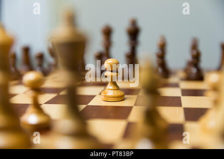 Pawn standing in the middle of chess board. Courage and leadership concept. - Stock Photo