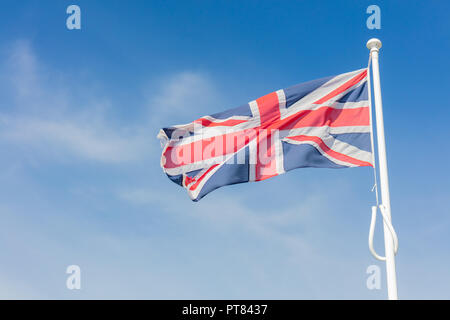 Union Jack Flag Flying From a Flagpole Under a Blue Sky - Stock Photo