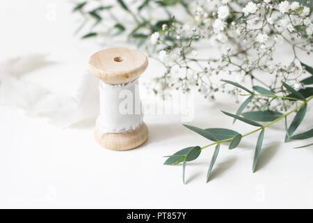 Feminine floral scene. Close-up of spool of silk ribbon, Eucalyptus parvifolia leaves and babys breath Gypsophyla flowers on a white table background. Wedding styled stock photography. Selective focus - Stock Photo
