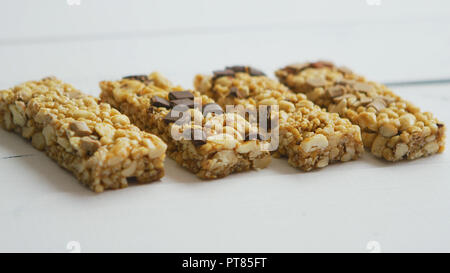 Granola bars with dried fruits wooden background - Stock Photo