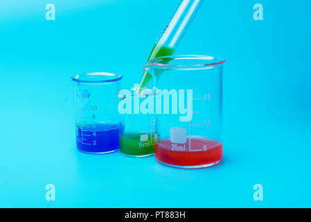 Laboratory glasses and pipette with green liquid. On a blue background with glasses of red and blue liquid. - Stock Photo