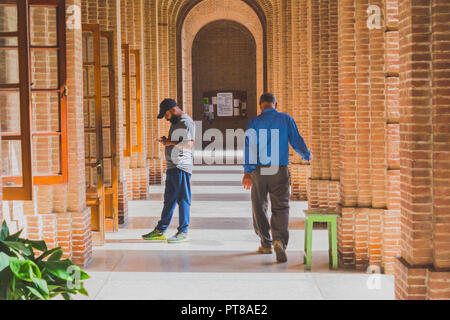 An aisle of a Greco-Roman architecture building with one young bearded man busy with the smartphone and one middle-aged man strolling down the aisle i - Stock Photo