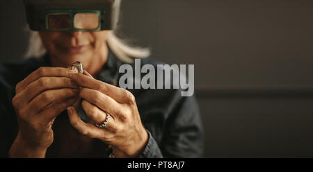 Female goldsmith inspecting jewelry using magnifying glass in workshop.  Woman jeweler inspecting diamond ring with magnifying glass. - Stock Photo