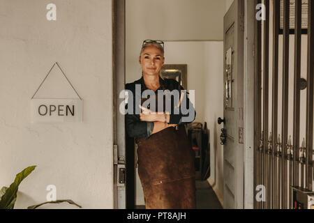 Portrait of senior female goldsmith standing at workshop door. Woman jeweler wearing apron and holding tools at workshop. - Stock Photo