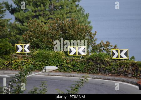 Dangerous bend on a narrow road through the mountain in Argegno, Lake Como, Italy - Stock Photo