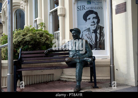 Statue of Sir Norman Wisdom sitting on a bench outside The Sefton Hotel, Douglas, Isle of Man - Stock Photo
