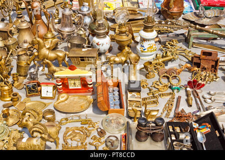 Lviv, Ukraine - July 10, 2015: Various things made of yellow metals for sale on a flea market. Decorative figurines, coins, lamps and other old and vi - Stock Photo