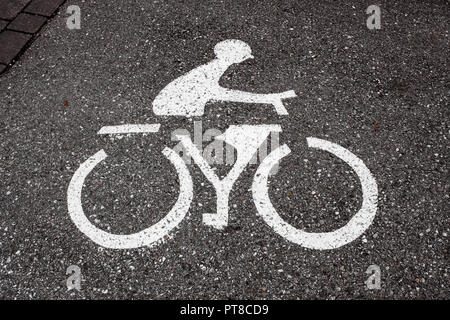 Bicycle lane sign on tarmac road. Traffic symbol  with bicycle and cyclist. - Stock Photo