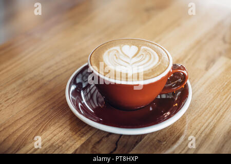 Close up hot cappuccino red coffee cup with heart shape latte art on wood table at cafe,Drak tone filter,food and drink - Stock Photo