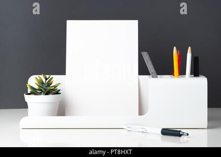 modern office stationery on white table and dark grey wall.pencil, notepad,ruler,pen and pencil box with plant.Mock up paper note for display of desig - Stock Photo
