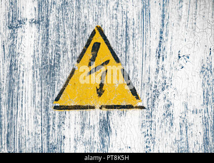 High voltage lightning sign in a yellow triangle on a painted wall. - Stock Photo