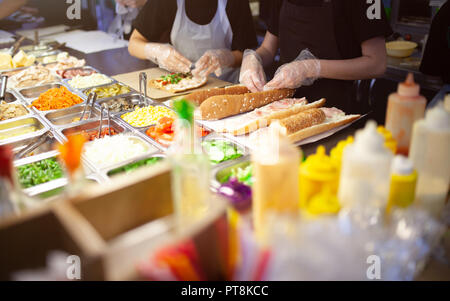 Female street vendor hands making sandwich outdoors. cuisine snacks, cooking fast food for commercial kitchen. The range of products for filling sandw - Stock Photo