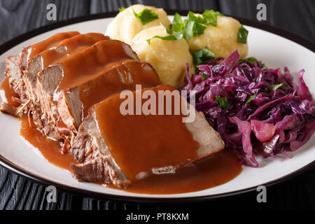 Slow Cooker Pot Roast Sauerbraten with spicy sauce, potato dumplings and red cabbage close-up on a plate. horizontal - Stock Photo