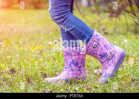 children's feet in rubber boots on yellowed dry grass in autumn - Stock Photo