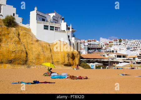 28 September 2018 Houses built on the sandstone cliffs in the Algarve. Sunbathing holiday makers on the beach on The Fisherman's Beach  in Albuferia - Stock Photo