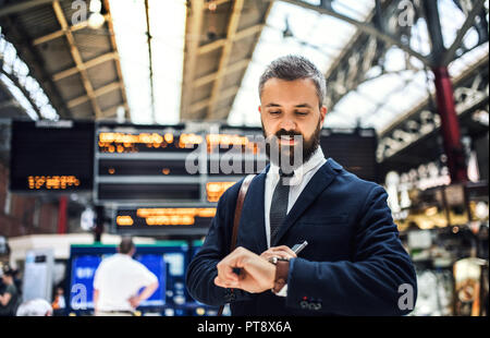 Businessman on the trian station in London, checking the time. - Stock Photo