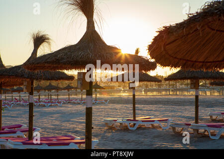 Empty chairs and straw umbrellas on the Alcudia beach in Majorca at sunrise - Stock Photo