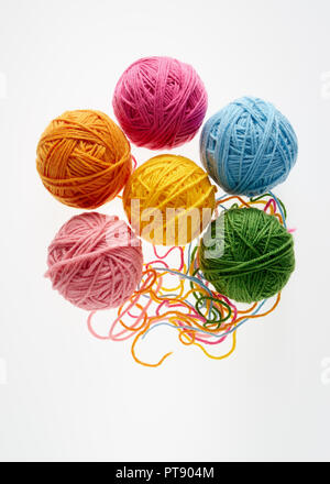 Colorful woolen balls over white background. Balls of wool partially unrolled. - Stock Photo