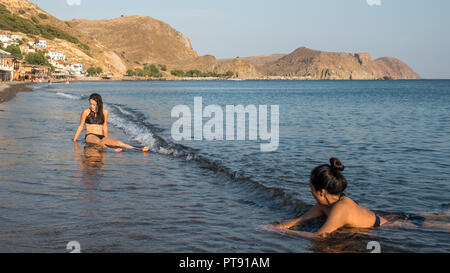 Women and Teenager sitting on the beach in Greece - Stock Photo