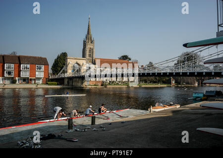 Members of the Marlow Rowing Club prepare for their morning row at Marlow on the river Thames, with its Victorian suspension bridge and All Saints Chu - Stock Photo