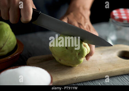 closeup of a young caucasian man cutting a quince fruit with a kitchen knife, on a chopping board, on a gray rustic wooden table - Stock Photo