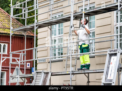 Trondheim, Norway - August 29th, 2018: A man working standing on a scaffolding in the city center of Trondheim. - Stock Photo