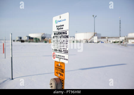 A warning sign for the Keystone Pipeline outside of TransCanada Hardisty Terminal 1, in Hardisty, Alberta, Canada, on December 7, 2013. Hardisty Terminal 1 is the starting point of the Keystone Pipeline. Construction is currently underway on TransCanada's Hardisty Terminal 2, which will be the starting point of the Keystone XL pipeline, which will transport oil from Alberta oilsands to markets in the United States. - Stock Photo