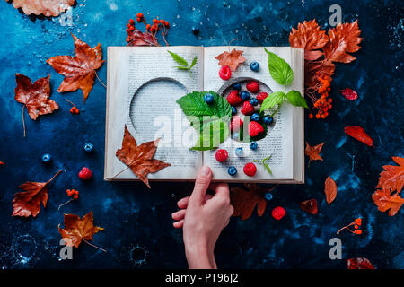 Secret storage book with last summer berries under an autumn rain. Preserving fleeting joys concept with copy space Stock Photo