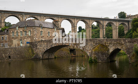 Old stone bridges over river La Rance in Dinan (France) on a cloudy day in summer - Stock Photo