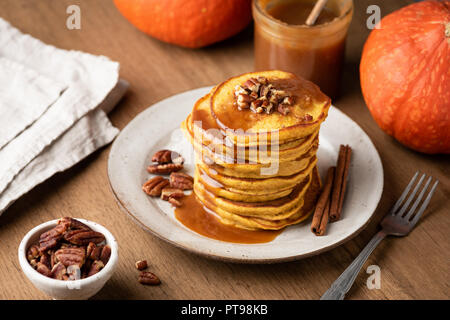 Homemade pumpkin pancakes with cinnamon, caramel and nuts on rustic wooden table - Stock Photo