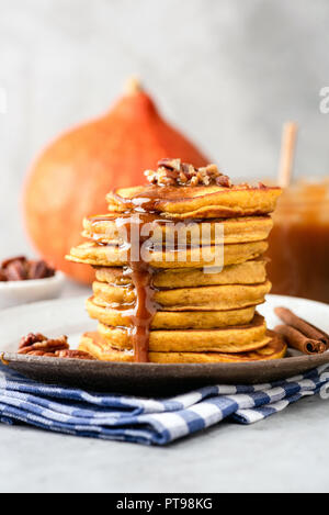 Pumpkin pancakes with caramel sauce and nuts on plate, closeup view, vertical composition - Stock Photo