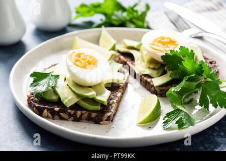 Toast with avocado and boiled egg on a plate, closeup view. Healthy breakfast, healthy eating or snack concept - Stock Photo